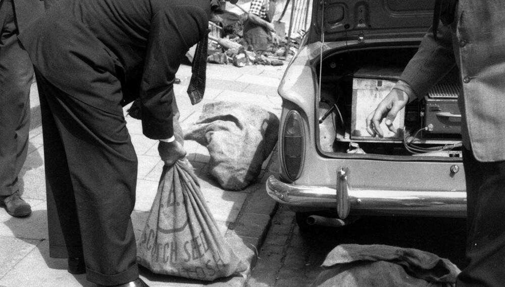 FELLENDE BEVIS: Politiet legger sekker med bevismateriale i bagasjerommet på en bil. Postsekkene som ble funnet i kjelleren på gården, knyttet stedet til ranet. Det er en gåte hvorfor ranerne ikke kvittet seg med «søpla» før de dro. Alle fingeravtrykkene i huset ble brukt som fellende bevis.