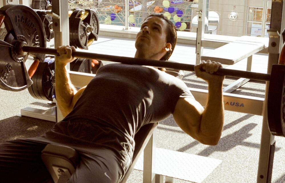 SKRÅBENK MED STANG: Hold vektstangen med et overhåndsgrep, og litt bredere enn skulderbreddes avstand. Løft stangen av, og hold den kontrollert med utstrakte armer over deg før du senker den kontrollert ned mot brystkassen. Press så stangen opp igjen, og repeter etter ønske.