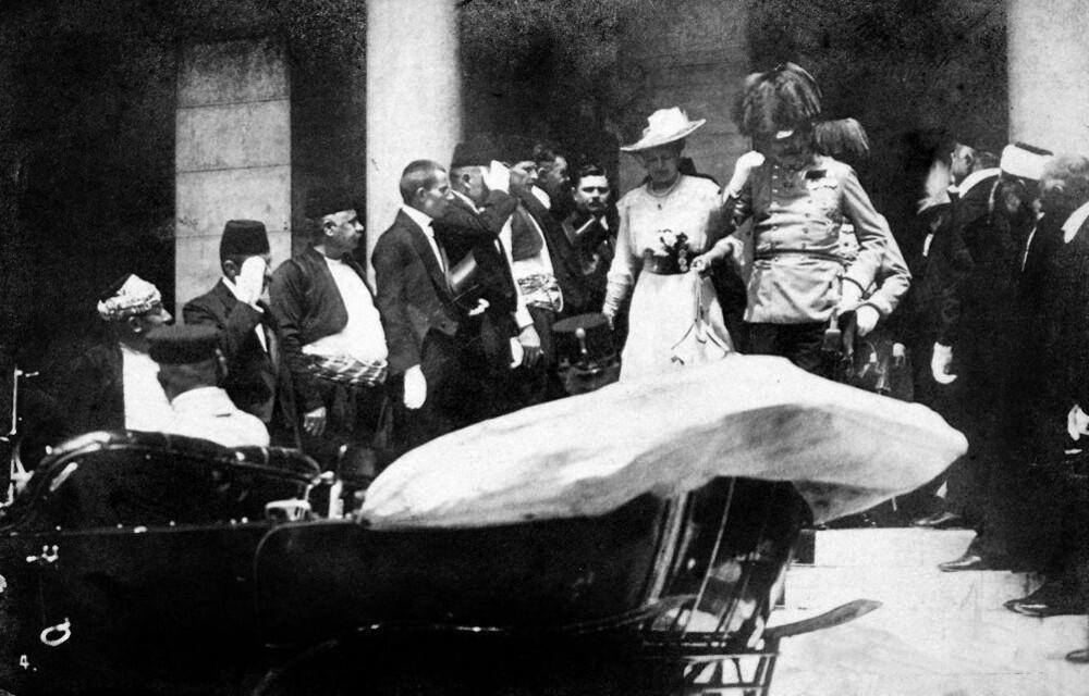 Franz Ferdinand og hans kone i ferd med å gå ombord i bilen ved rådhuset i Sarajevo. Minutter senere var begge skutt av Garvilo Princip, en bosnisk serber som var medlem av en organisasjon kalt Unge Bosnia. Organisasjonen var en terrororganisasjon som jobbet for et samlet Jugoslavia, fritt fra Østerrike-Ungarn, og hadde indirekte tilknytninger til den serbiske regjeringen.