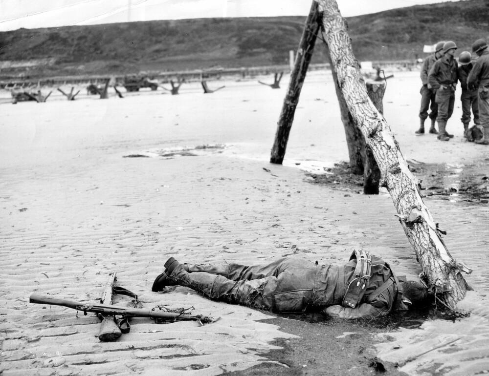 TUSENVIS AV DØDE: En fallen amerikansk soldat ligger i enden av en bjelkerampe, en av over 3700 sperringer tyskerne plasserte på stranda. Da 6. juni går på hell, har landgangen på Omaha Beach kostet amerikanerne nærmere 2400 døde og sårede, mens tyskernes tap er mer usikre – trolig i overkant av 1000.