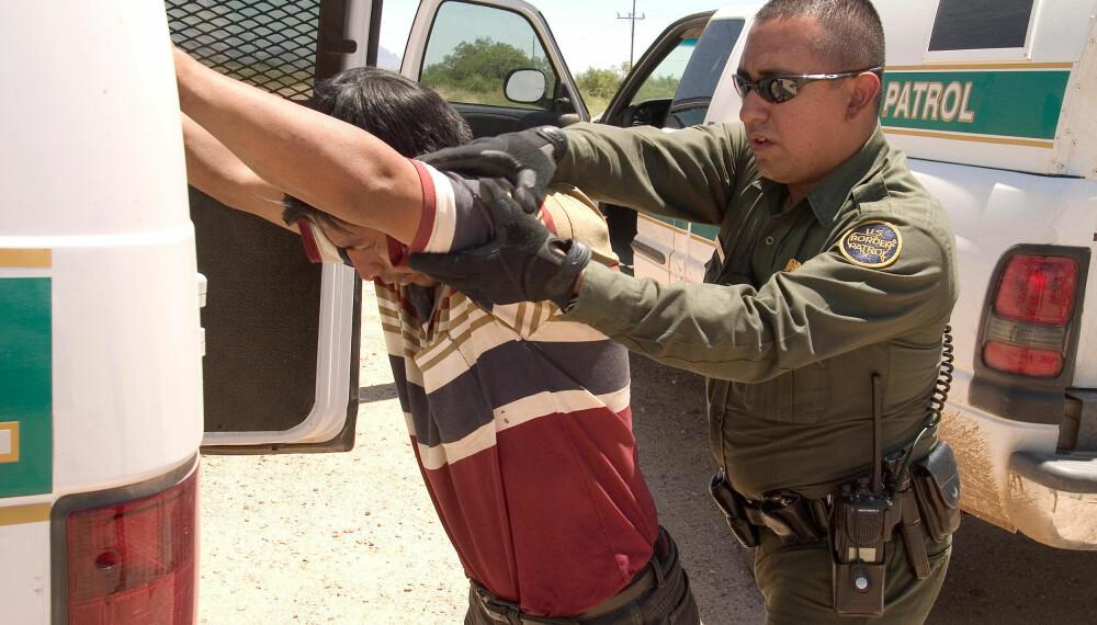ANHOLDT: En mann mistenkt for å ha tatt seg inn i landet ulovlig blir anholdt og ransaket av en agent fra US Customs and Border Protection.