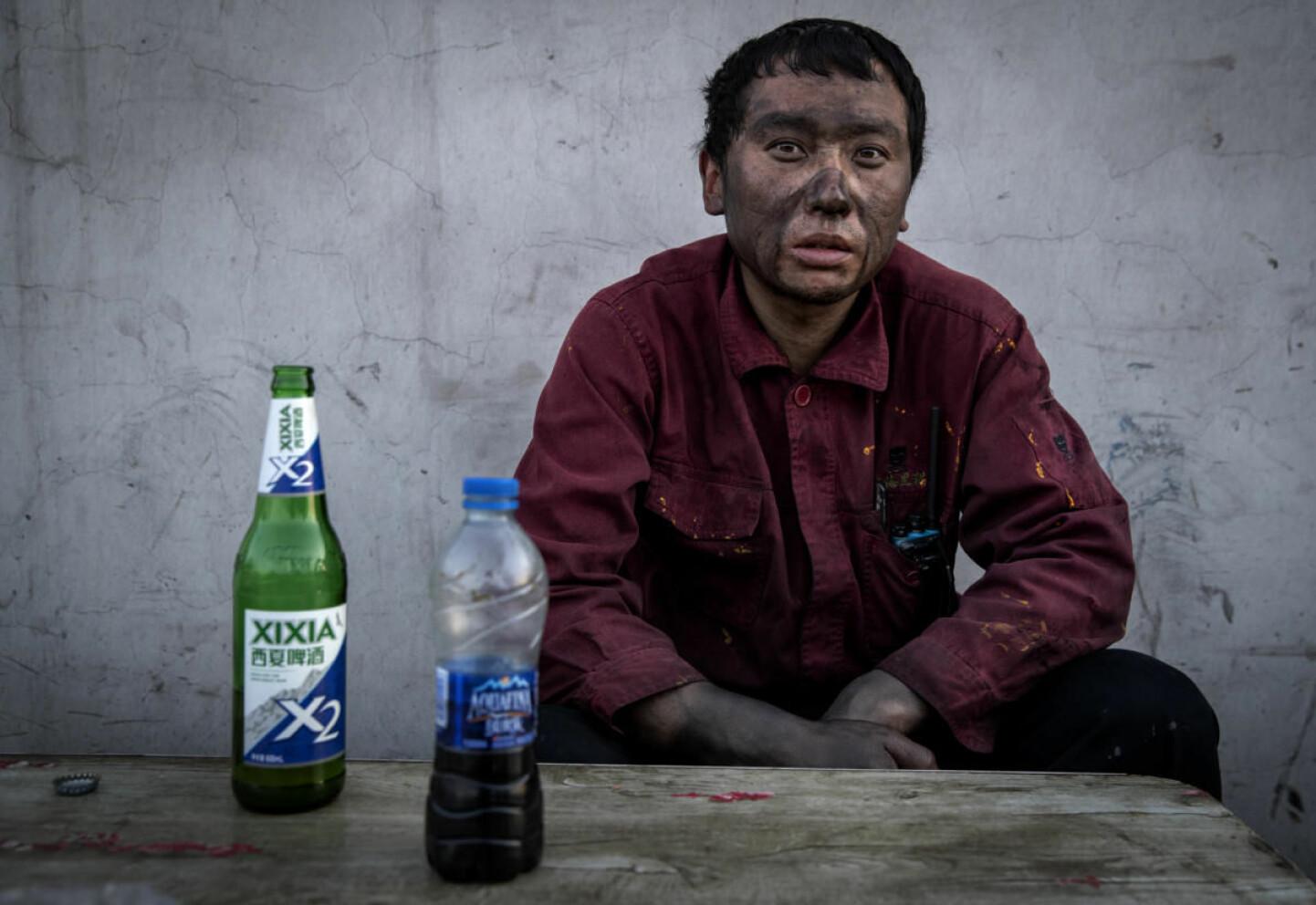 Svart arbeid: Han jobber  med tjære i et kraftverk som fyres med kull. Og er med på å betale prisen for fjerning av smog i kinesiske torbyer. Skiftene hans er 12 timer, syv dager i uka.