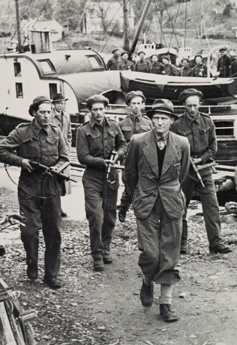 <b>Etterpå:</b> Den tidligere betjenten Johan Bjørgan fra det norske nazipolitiet blir sommeren 1945 tatt i land i Telavåg under skarp bevoktning.