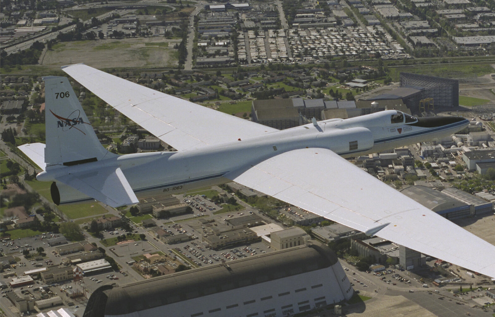 <b>HANGAR ONE:</b> EtLockheed ER-2 (basert på spionflyet U-2) flyr over Moffett Federal Airfield i 1996. Den store bygningen er Hangar One.