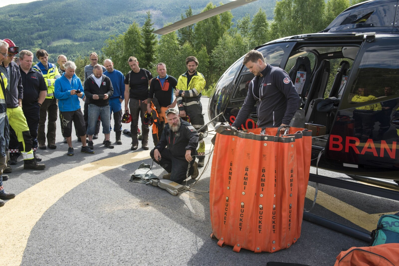 <b>SAMARBEID:</b> Pilot John-Arne Hellesø og lastemann Nils Martin Holden demonstrerer vannbøtta for brannfolk i Hallingdal.