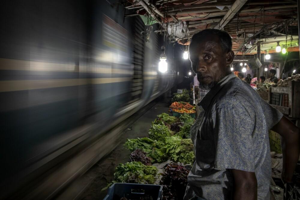 <b><SPAN CLASS=BOLD><STRONG>DUNDRER FORBI:</b></strong></span> Grønnsaksselger Mohidul venter tålmodig mens et tog passerer i høy fart. Han rakk akkurat å flytte boden sin før toget kom.
