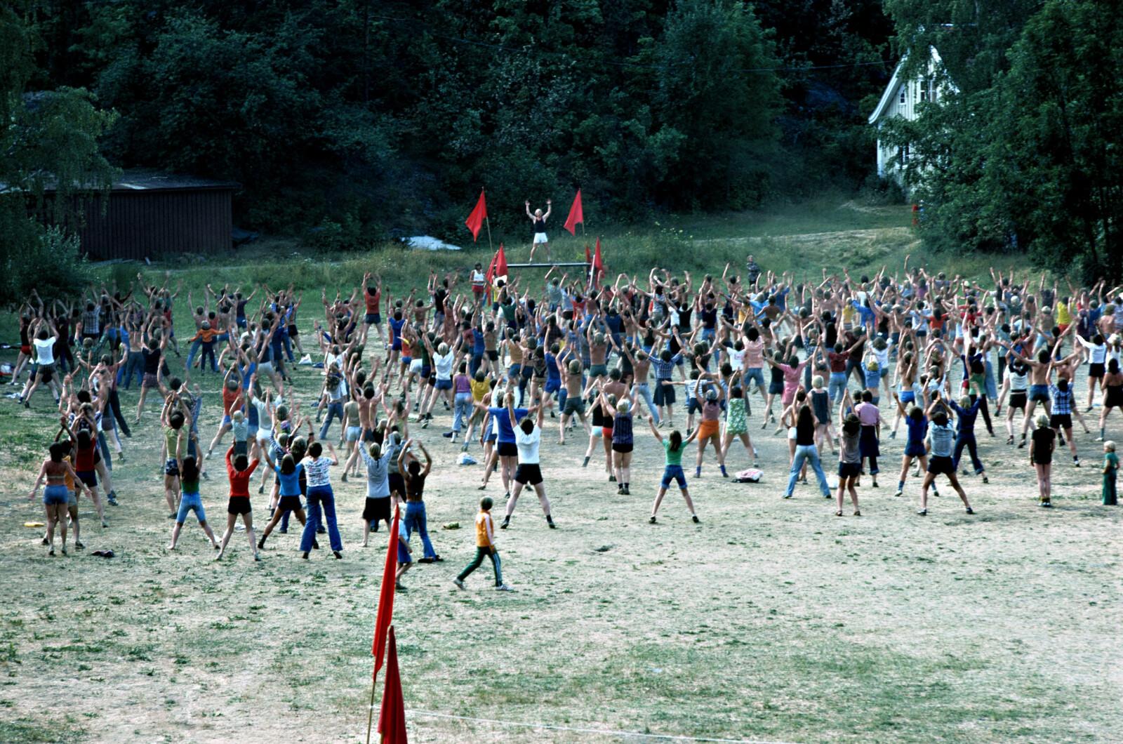 """<b>FELLESTRENING UNDER RØDE FANER</b> AKP-medlemmer gjør felles morgengymnastikk under en av sine sommerleirer på 1970-tallet. Målet var å bli """"fit"""" for væpna revolusjon."""