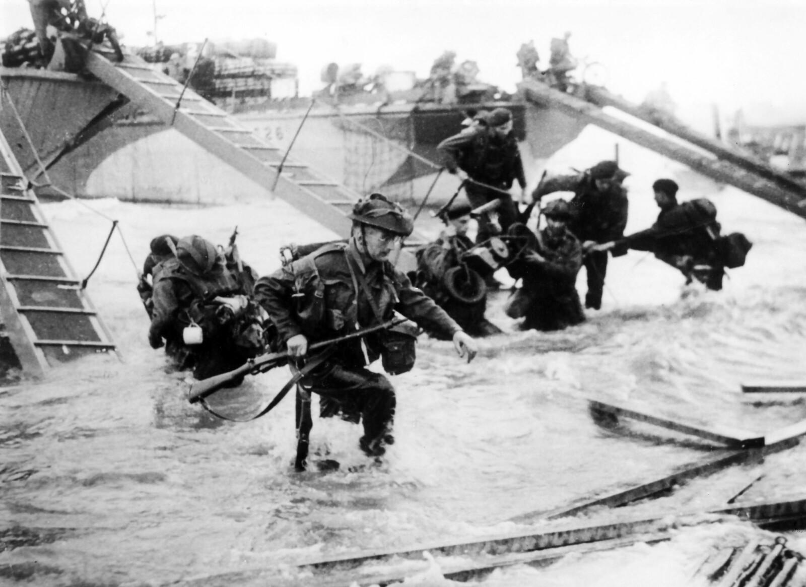 <b>INN I STRIDEN:</b> Britiske marinesoldater vasser i land på Juno Beach på D-dagen, 6. juni 1944. Værvarselet til nord-mannen Sverre Petterssen var sterkt medvirkende til at landgangen ikke fant sted i full storm ett døgn tidligere. Den tyske motstanden kostet 2000 soldater livet på strendene i Normandie.