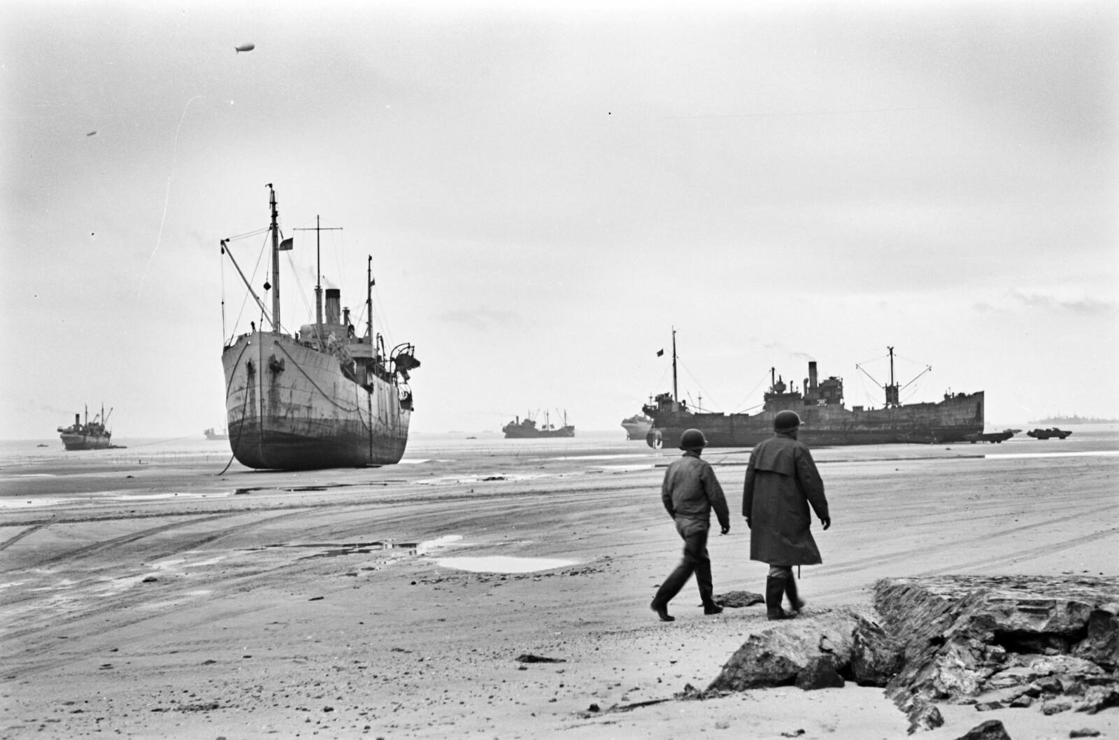 <b>PÅ TRYGG GRUNN:</b> De norske handelsskipene Fagerbro (t.v.) og Heien (t.h.) var blant de 50 norske sivile fartøyene som bidro til at invasjonen i Normandie lyktes. Her under lossing ved lavvann utenfor det amerikanske avsnittet av stranden.
