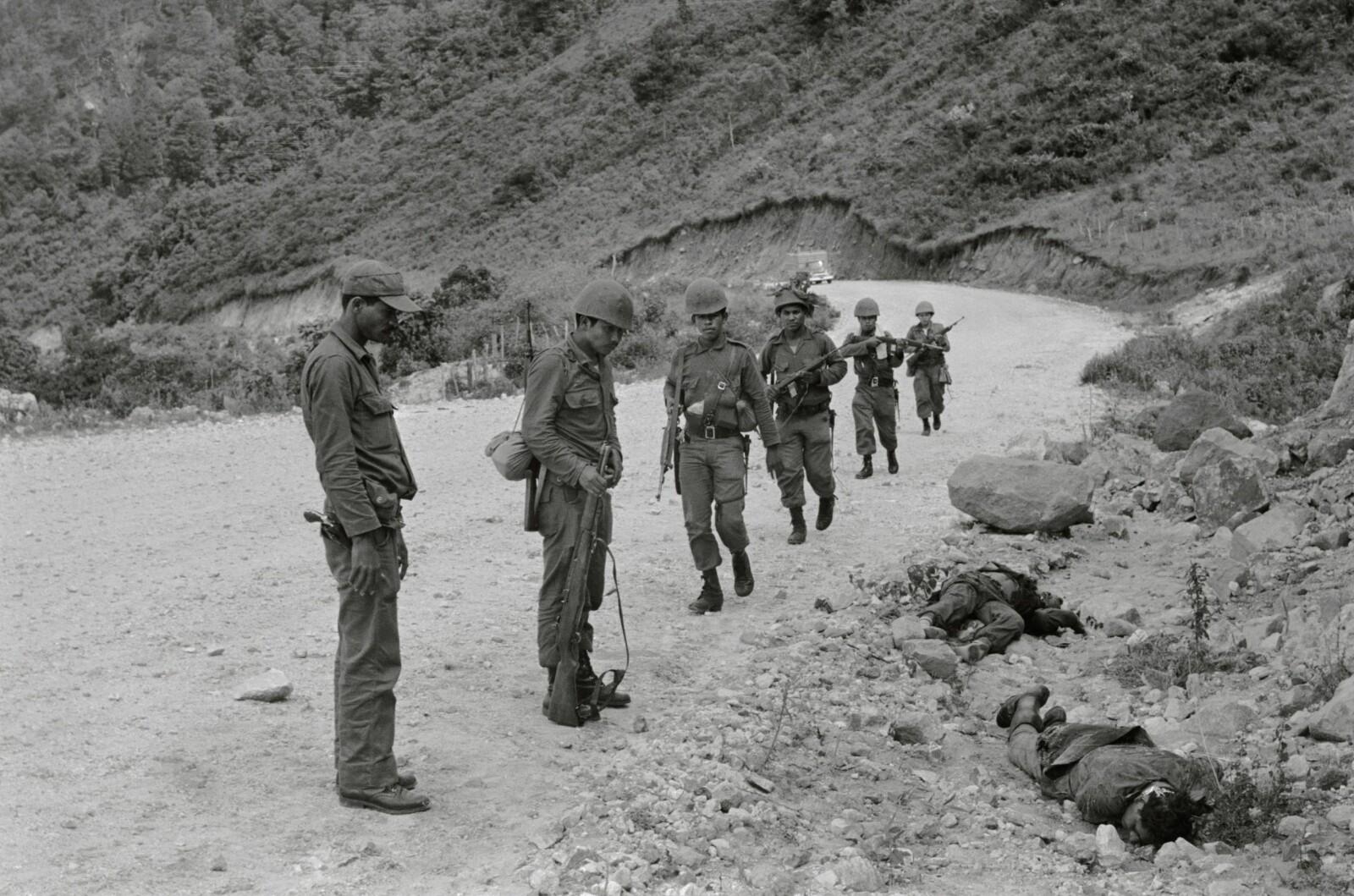 <b>DØDENS GRØFT:</b> Honduranske soldater kikker på falne fiender fra El Salvadors hær etter en trefning under den såkalte Fotballkrigen for 50 år siden.