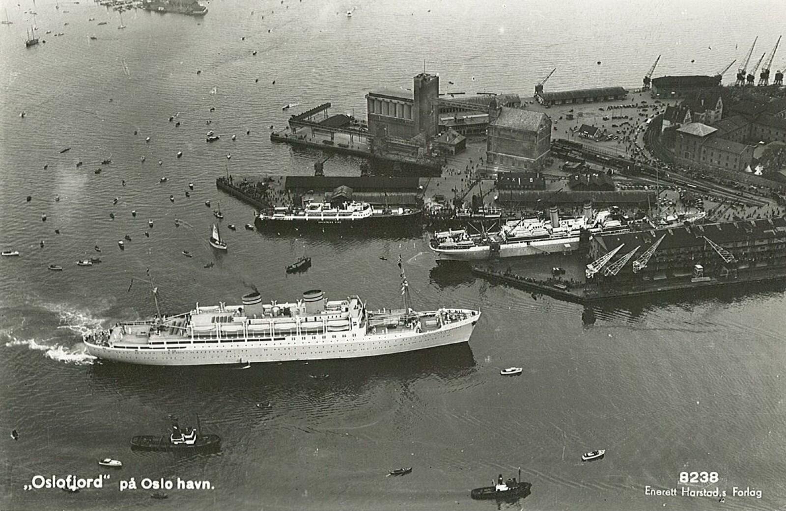 <b>VIPPETANGEN:</b> Dette bildet skal være tatt i løpet av perioden fra «Kronprins Olav» ble satt i rute og til hun ble lagt i opplag i Danmark. I forgrunnen ses amerikabåten SS «Oslo-fjord». Ved Den Norske Amerika-linjes kai ligger SS «Bergens-fjord», og ved utstikker II ses MS «Kronprins Olav».
